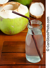 Coconut water drink in bottle open with straw on wooden table