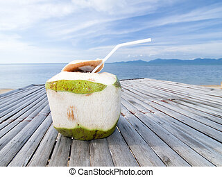 Coconut Water Drink on bamboo table with sea background