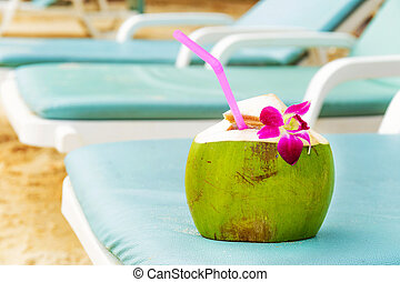 Coconut with drinking straw on beach bench
