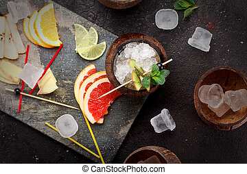 Coconut with ice and fresh fruits (grapefruit, kiwi, orange ) and mint over concrete background.