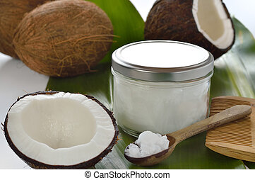 Coconuts and organic coconut oil in a glass jar on white background. Hair treatment.