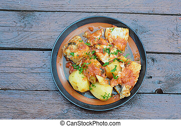 cod cooked in a pan with tomato, olives and potatoes