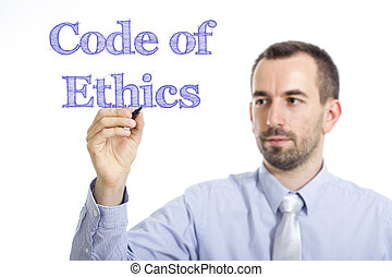 Code of Ethics - Young businessman writing blue text on transparent surface