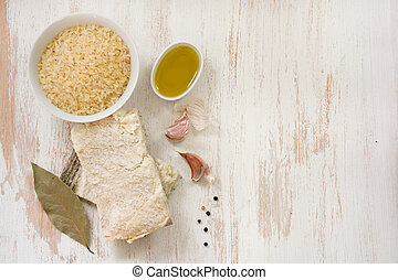codfish with rice, olive oil and garlic on white wooden background