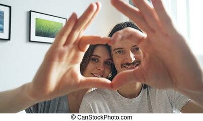 coeur, couple, regarder, leur, appareil photo, mains, portrait, confection, sourire