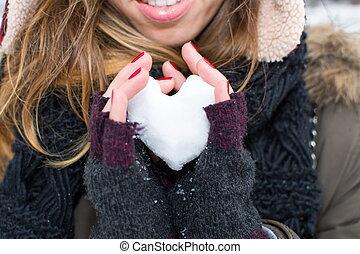 coeur, femme, formé, boule de neige, tenant mains