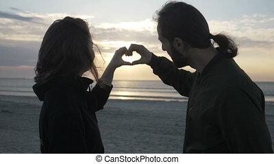 coeur, lent, regarder, couple, séance, jeune, mouvement, leur, forme, coucher soleil, séduisant, mains, confection, plage