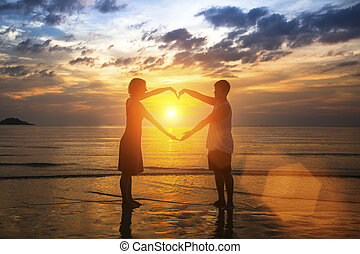 coeur, silhouette, couple, jeune, forme, surprenant, tenant mains, plage, sunset.