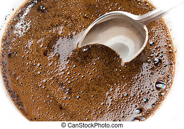 Cofee - Teaspoon in a thick foam of ground coffee