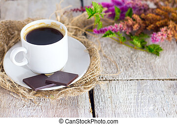 coffe, chocolate and fresh flower on white wooden background.