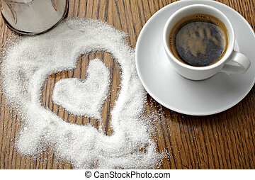 close up of a coffe cup and heart shape in sugar on table