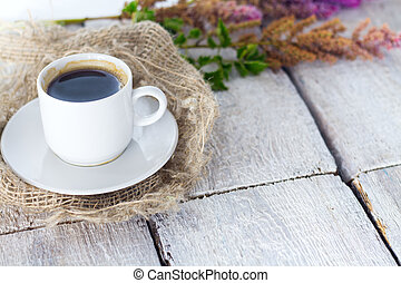 coffe with fresh flowers on white rustic background.