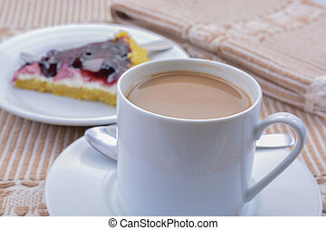 Coffee - A cup of coffee and an blue berries cheese cake.