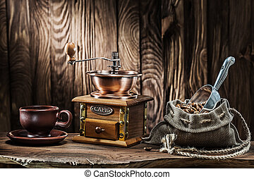 coffee accessories brown clay cup vintage wooden mill and sack with beans scoop on old wood background