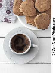 Coffee and cookies on white wooden table