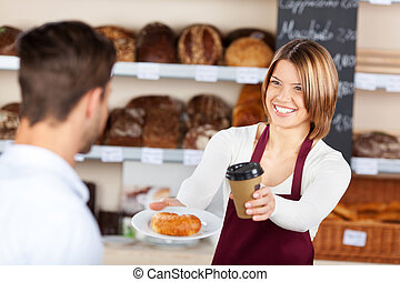 Coffee and croissant - Female baker giving coffee and ...