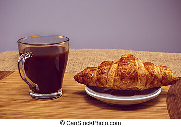Coffee and croissant for breakfast on rustic wooden table