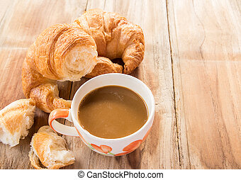Coffee and croissant for breakfast on wooden table