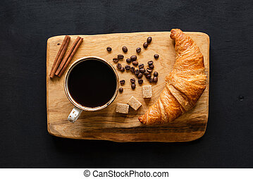 Coffee and croissant on wooden board, top view