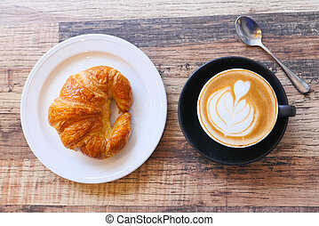 Coffee and croissant on wooden table, top view .