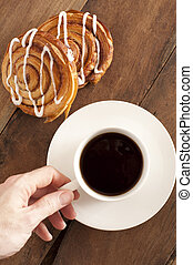 Overhead view of a mans hand reaching out to take a cup of rich espresso coffee and fresh Danish pastries for breakfast