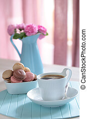 Cup of black coffee and macarons on a table