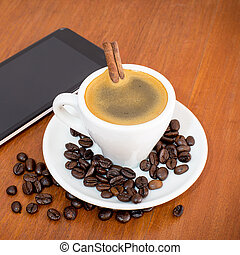 coffee and tablets on a wooden table in coffee shop