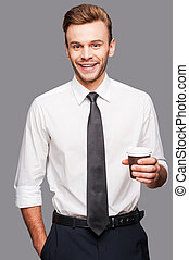 Coffee and work.  Cheerful young man holding a cup of coffee while standing against grey background