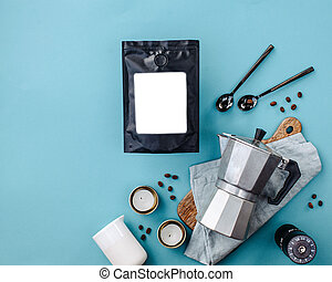 coffee bag with a white label, geyser coffee machine and coffee beans on a blue background flatlay