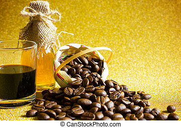 Coffee beans and Black coffee cup and Honey in the bottleon on golden background.