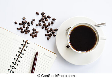 Coffee beans and cup of coffee on white with notebook and pen