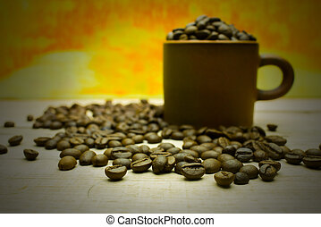 coffee beans and cup on the wooden table on gold background