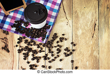 coffee beans and cup on the wooden table.