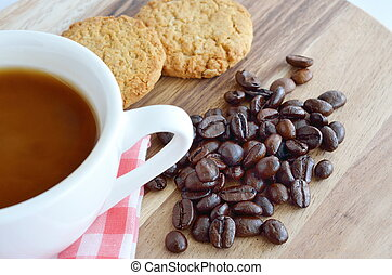 Coffee beans and cup with cookies on wooden background