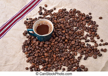 Coffee beans and green cup on textured background. copy space