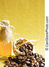 Coffee beans and Honey in the bottleon on golden background.