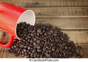 coffee beans and red cup on the wooden table background