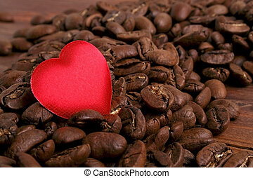 Coffee beans and red heart on wooden background