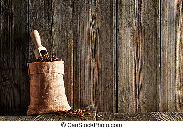 Coffee beans and scoop in sack on wooden table