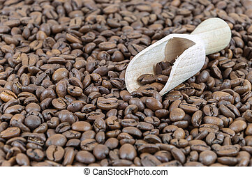 Wooden shovel on a background made of coffee beans