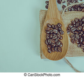 Coffee beans and wooden spoon on sack surface. Filter effect retro vintage style