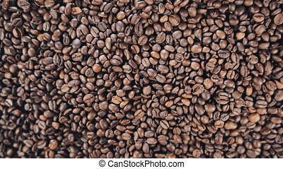 Coffee beans are on the table. Rotate. Slow motion
