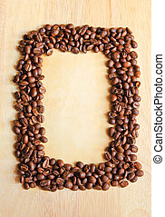 Coffee beans as frame with old paper for notes on the wooden background