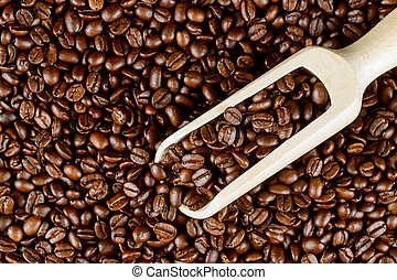 Coffee beans background with wooden spoon.