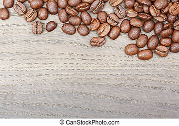 Coffee beans border on old oak table.