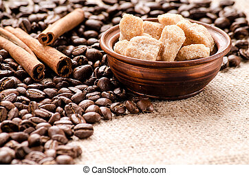Coffee beans, cane sugar and cinnamon on the table