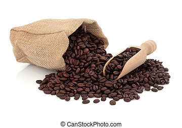 Coffee beans in a wooden scoop and spilling out from a hessian bag, over white background.