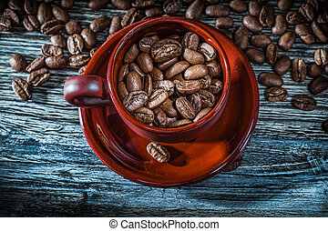 Coffee beans cup saucer on wooden board