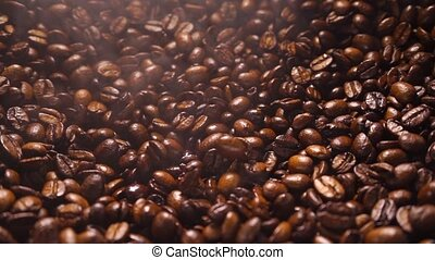 Coffee beans falling down on a a pile of smoking roasted coffee beans