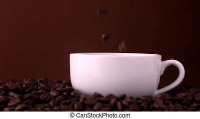 Coffee beans falling into white cup